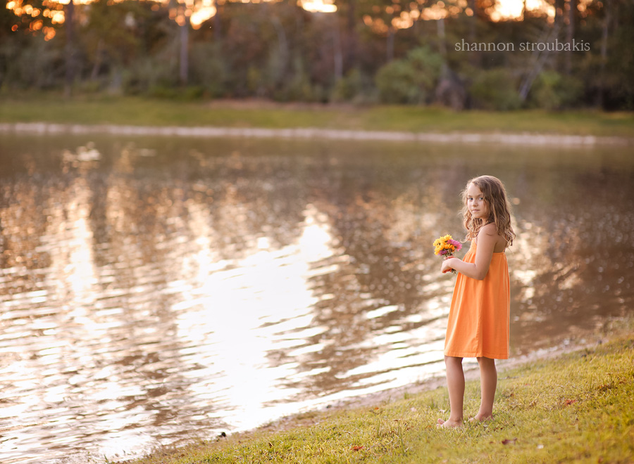 photo of a little girl with long hair in a sundress outside by a lake with a bouquet of flowers
