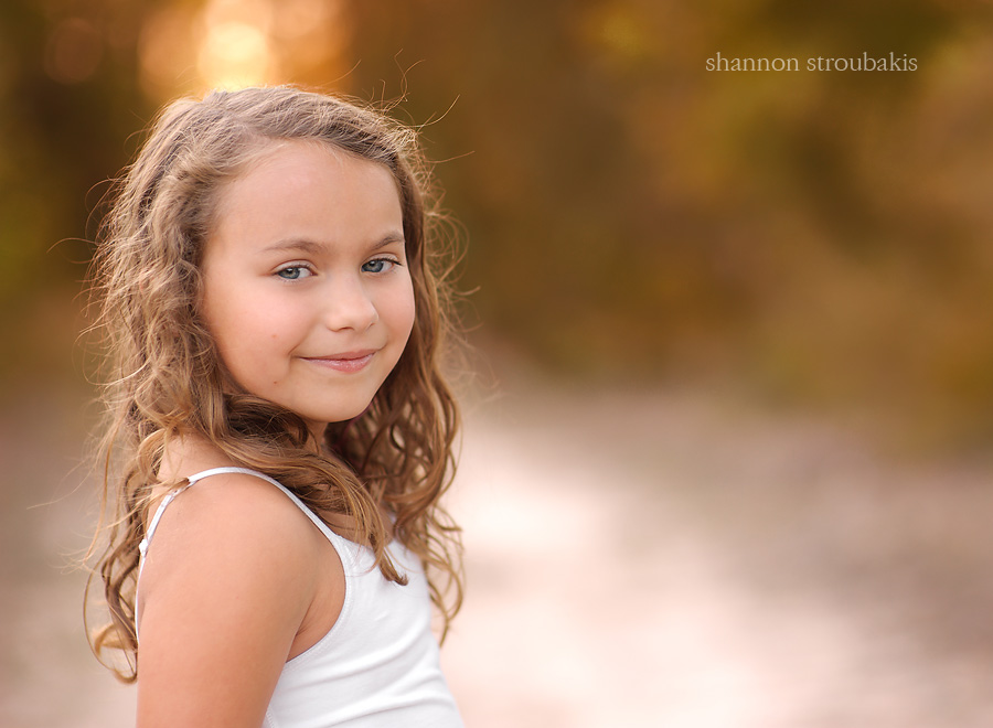 close up image of a little girl smiling outside with warm autumn colours