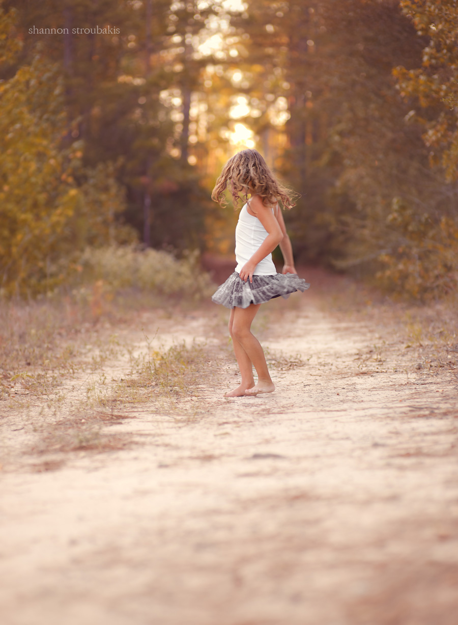 little girl with long curly hair and skirt twirling on a dirt path at sunset