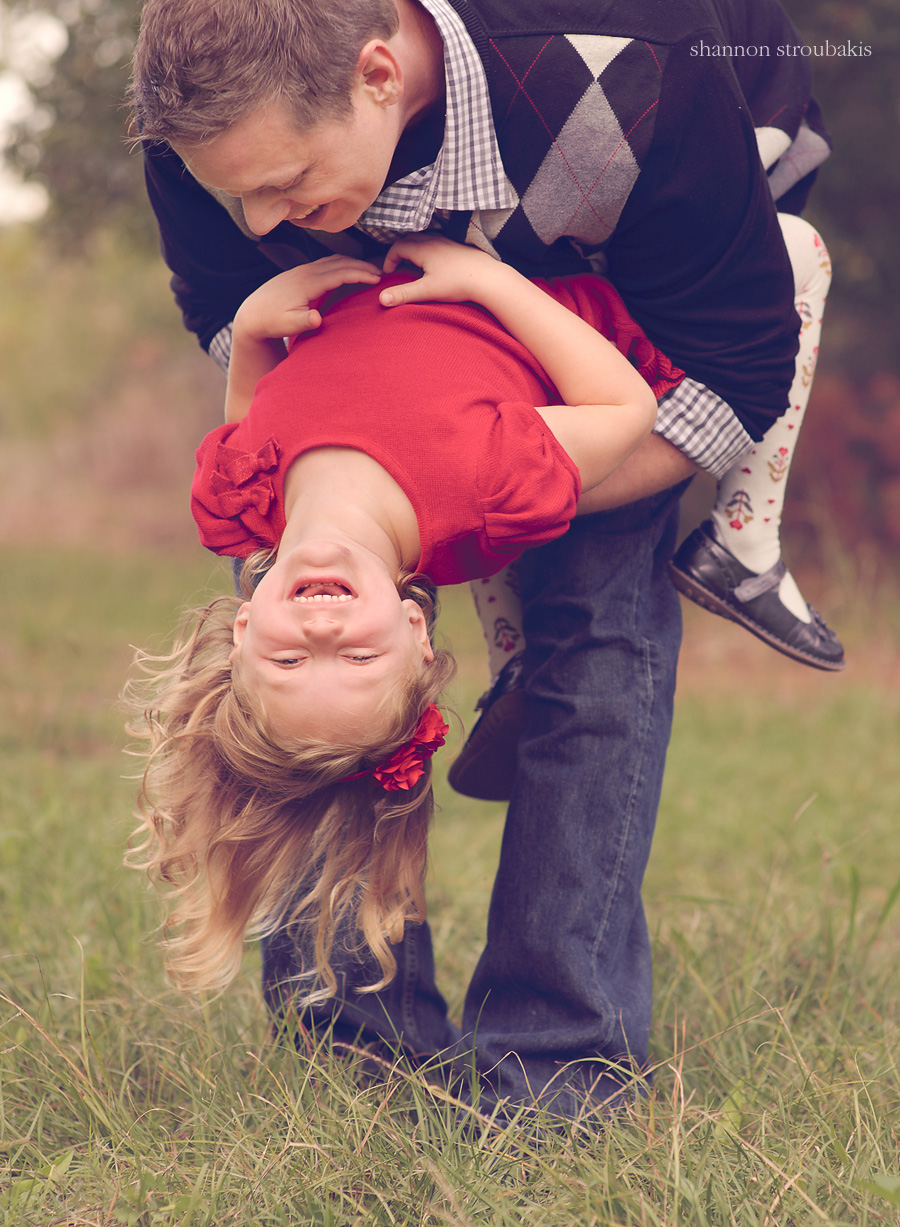 Dad swinging daughter upside down and laughing picture of a family session